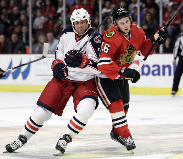 FILE - In this Oct. 29, 2011, file photo, Columbus Blue Jackets' Vinny Prospal, left, and Chicago Blackhawks' Marcus Kruger (16) battle for position during the first period of an NHL hockey game in Chicago. A new team president, a sort of new head coach and six or seven new faces on the roster have the Blue Jackets looking for improvement as they head into the new, shortened NHL season. (AP Photo/Nam Y. Huh, File)