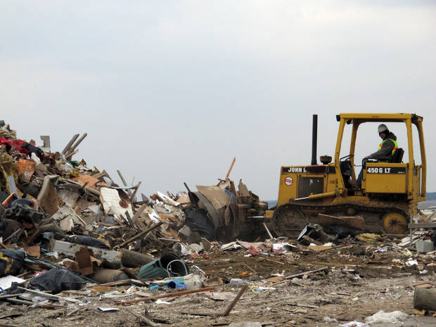 A worker uses a bulldozer to push debris from Superstorm Sandy into a large pile in Lavallette N.J.  Friday, Jan. 4, 2012, shortly before Congress voted to approve aid for storm victims. (AP Photo/Wayne Parry)