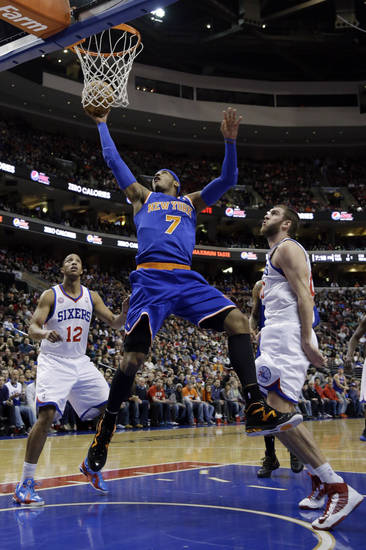 New York Knicks' Carmelo Anthony, center, shoots between Philadelphia 76ers' Evan Turner, left, and Spencer Hawes during the first half of an NBA basketball game on Saturday, Jan. 26, 2013, in Philadelphia. (AP Photo/Matt Slocum)