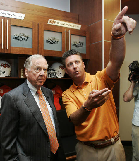 Oklahoma State football coach Mike Gundy, right, points out some of the features of the new locker room to T. Boone Pickens, left, while standing in front of a locker reserved for Pickens, Monday, Aug. 17, 2009, in Stillwater, Okla. Through a series of donations, Pickens provided the bulk of the funding for a $286 million stadium overhaul. (AP Photo/Sue Ogrocki)   ORG XMIT: OKSO107