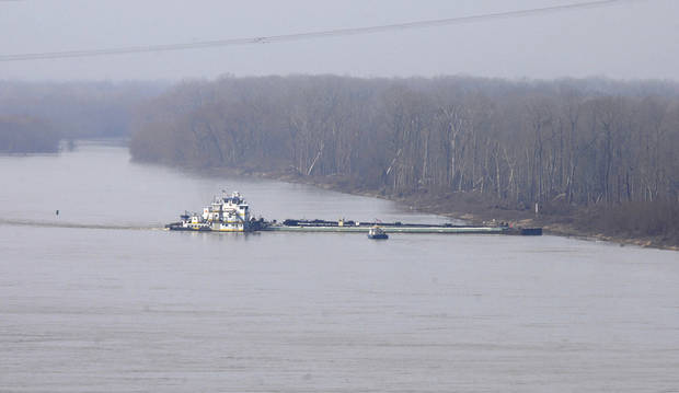 CORRECTS DATE TO JAN. 28, NOT JAN. 18 - The towboat Natures Way Endeavor, background, banks a barge against the western bank of the Mississippi River, Monday, Jan. 28, 2013.  Cleanup crews with booms skimmed oily water from the Mississippi River Monday, a day after a barge with more than 80,000 gallons of oil struck a railroad bridge near Vicksburg, spreading a sheen of light crude that kept part of the waterway shut to ship traffic Monday, authorities said. (AP Photo/Eli Baylis)