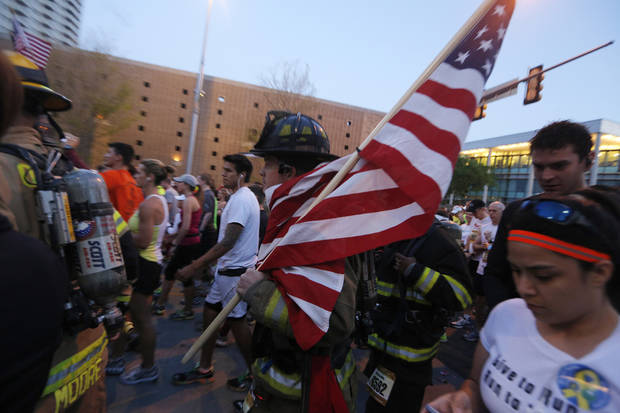 A fireman carries an American flag at the start of the Oklahoma City Memorial Marathon in Oklahoma City, Sunday, April 28, 2013.  Photo by Garett Fisbeck, For The Oklahoman