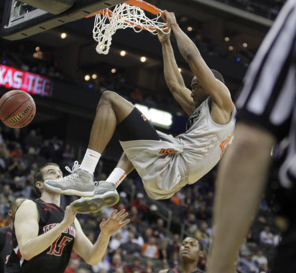 Oklahoma State&#039;s Markel Brown (22) dunks over Texas Tech&#039;s Robert Lewandowski (15) during the Big 12 tournament men&#039;s basketball game between the Oklahoma State Cowboys and the Texas Tech Red Raiders at the Sprint Center, Wednesday, March, 7, 2012. Photo by Sarah Phipps, The Oklahoman