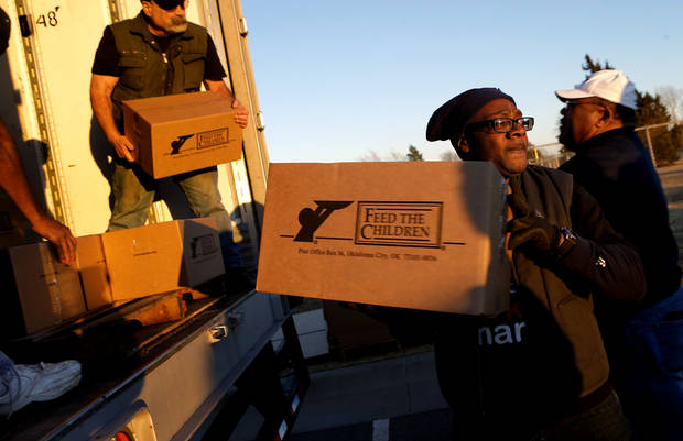 Feed The Children volunteer Wayne Richmond unloads a 25-pound box of food to hand out to those in need outside Douglass High School on Tuesday. Photo by Bryan Terry, The Oklahoman <strong>BRYAN TERRY - THE OKLAHOMAN</strong>