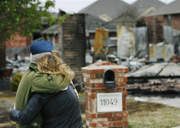 Laura Burgwyn is  hugged by Canadian Air Force CWO James Dawson as they look at what remains of Burgwyn's home Friday morning, April 10, 2009.  Laura and her husband, Roger, are scheduled to return to Canada in two months. Roger Burgwyn is a member of the Canadian Air Force stationed at Tinker AFB.  Photo by Jim Beckel, The Oklahoman