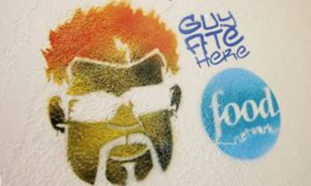 A Guy Fieri logo is seen on the wall inside Nic's Grill in this August 2009 photo by Paul B. Southerland.