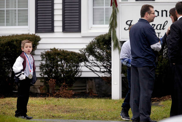 A young boy looks on as mourners arrive for the funeral service of Sandy Hook Elementary School shooting victim, Jack Pinto, 6, Monday, Dec. 17, 2012, in Newtown, Conn. Pinto was killed when a gunman walked into Sandy Hook Elementary School in Newtown Friday and opened fire, killing 26 people, including 20 children.(AP Photo/David Goldman) ORG XMIT: CTDG120