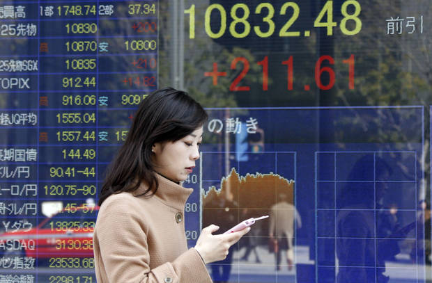 A woman walks by an electronic stock board of a securities firm in Tokyo, Friday, Jan. 25, 2013.  Japan�s benchmark stock index jumped about 2 percent Friday after the country�s currency continued to slide against the dollar. (AP Photo/Koji Sasahara)