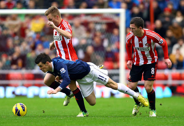 Tottenham Hotspurs' Gareth Bale, center, vies for the ball with Sunderland's Craig Gardner, right, and Sebastian Larsson, left, during their English Premier League soccer match at the Stadium of Light, Sunderland, England, Saturday, Dec. 29, 2012. (AP Photo/Scott Heppell)