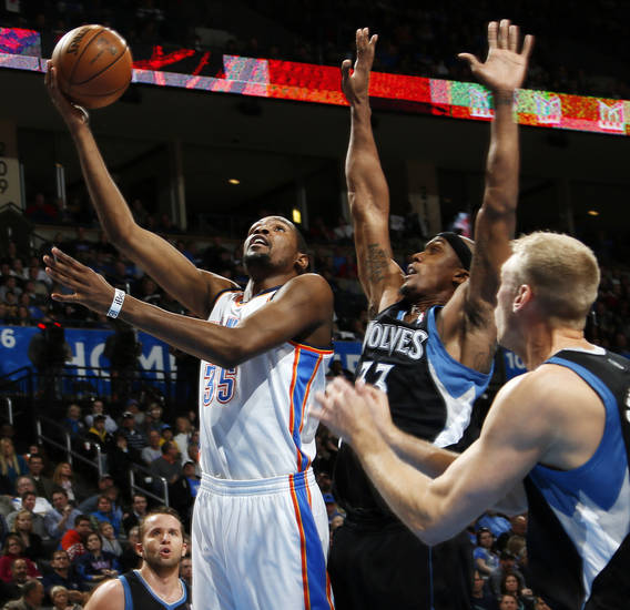 Oklahoma City's Kevin Durant (35) lays up a shot past Minnesota's Dante Cunningham (33) and Greg Stiemsma (34) during an NBA basketball game between the Oklahoma City Thunder and Minnesota Timberwolves at Chesapeake Energy Arena in Oklahoma City, Friday, Feb. 22, 2013. Photo by Nate Billings, The Oklahoman