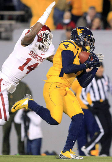 West Virginia's Stedman Bailey (3) catches a pass for a touchdown as Oklahoma's Aaron Colvin (14) attempts to tackle during their NCAA college football game in Morgantown, W.Va., on Saturday, Nov. 17, 2012. (AP Photo/Christopher Jackson)