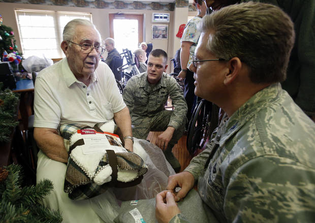 World War II U.S. Navy veteran John Bailes, left, talks with National Guardsman Samuel Winter, center, and Col. Jeff Pickard at a holiday party Friday at the Norman Veterans Center sponsored by the 507th Air Refueling Wing at Tinker Air Force Base. PHOTO BY STEVE SISNEY, THE OKLAHOMAN <strong>STEVE SISNEY</strong>