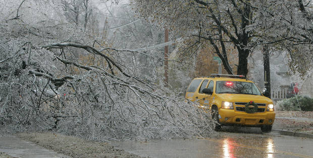 WINTER / COLD / WEATHER / ICE STORM / DAMAGE / AFTERMATH: An emergency vehicle goes around a downed tree near the corner of Dakota Street and Berry Road in Norman, OK. Monday, Dec. 10, 2007. BY JACONNA AGUIRRE/THE OKLAHOMAN. ORG XMIT: KOD