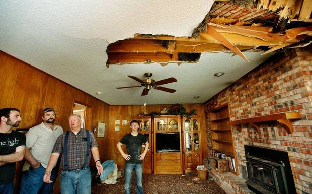 Homeowner Joseph Reneau, third from left, shows friends the damage caused to his home's family room after the chimney toppled onto the roof, creating a large hole in the ceiling. An earthquake late Saturday night caused extensive damage to the two-story ranch-style home of Joseph and Mary Reneau near the community of Sparks in Lincoln County. Photo by Jim Beckel, The Oklahoman
