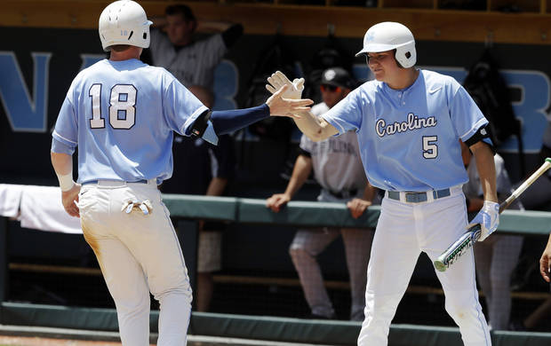 North Carolina's Colin Moran (18) is congratulated by Michael Russell (5) after scoring in the sixth inning of an NCAA college baseball tournament super regional game against South Carolina in Chapel Hill, N.C., Tuesday, June 11, 2013. North Carolina won 5-4 to advance to the College World Series. (AP Photo/Gerry Broome)