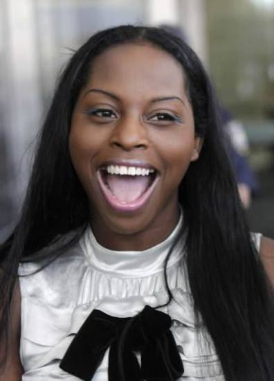 Inga Marchand, also known as Foxy Brown, laughs while talking to reporters after leaving court in New York, Tuesday, July 12, 2011. Charges that rapper Foxy Brown violated a court order by mooning her neighbor have been dropped. (AP Photo/Seth Wenig)