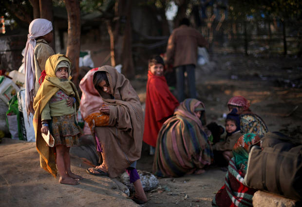 Homeless children wrapped in warm clothes huddle near a pavement on a cold morning in New Delhi, India, Wednesday, Jan. 9, 2013. North India continues to face below average weather conditions with dense fog affecting flights and trains. More than 100 people have died of exposure as northern India deals with historically cold temperatures. (AP Photo/Altaf Qadri)