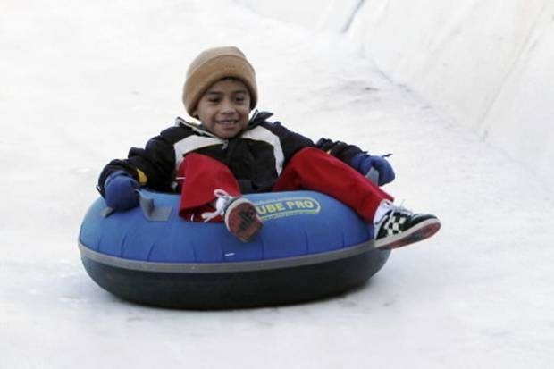 Eight-year-old Daniel Dobson begins a run as snow tubing starts at the Chickasaw Bricktown Ballpark in Oklahoma City, OK, Friday, December 21, 2012. By Paul Hellstern, The Oklahoman Archive
