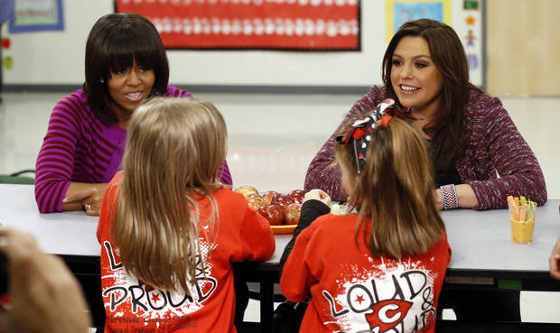 "First lady Michelle Obama and Food Network chef Rachel Ray discuss the lunches students from the Eastside and Northside Elementary Schools receive ""Let's Move!"" program at the Clinton, Miss., schools Wednesday, Feb. 27, 2013. The pair visited with the children and conducted a cooking contest between the schools' chefs. (AP Photo/Rogelio V. Solis)"