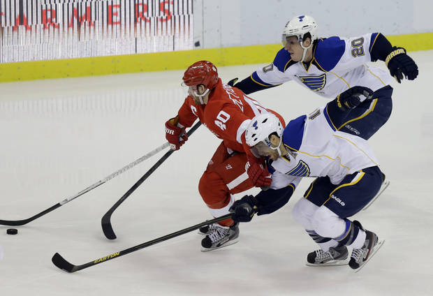 Detroit Red Wings center Henrik Zetterberg (40), of Sweden, controls the puck between the defense of St. Louis Blues left wing Alexander Steen (20) and center Andy McDonald during the third period of an NHL hockey game in Detroit, Friday, Feb. 1, 2013. (AP Photo/Carlos Osorio)