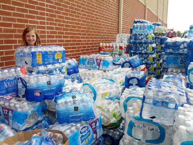 9-year-old Emma Kitchel can hardly see over the donations of water outside her grandmother's church.