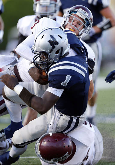 Edmond Memorial's Sam Kreutzer, top, and Tasden Ingram tackle Edmond North's Michael Farmer during the high school football game between Edmond North and Edmond Memorial at Wantland Stadium in Edmond, Okla., Friday, Aug. 31, 2012. Photo by Sarah Phipps, The Oklahoman