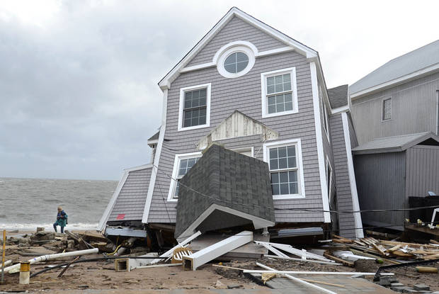 A woman walks past a house collapsed by superstorm Sandy in East Haven, Conn. on Tuesday, Oct. 30, 2012. (AP Photo/Jessica Hill) ORG XMIT: CTJH110