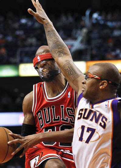 Chicago Bulls' Richard Hamilton, left, is fouled in the face by Phoenix Suns' P.J. Tucker (17) during the first half of an NBA basketball game, Wednesday, Nov. 14, 2012, in Phoenix. (AP Photo/Ross D. Franklin)