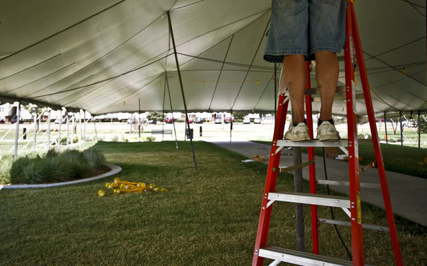 A member of the setup crew works atop a ladder hanging lights during setup for the Arts Festival Oklahoma at Oklahoma City Community College on Tuesday, Aug. 31, 2010, in Oklahoma City, Okla.  Photo by Chris Landsberger, The Oklahoman