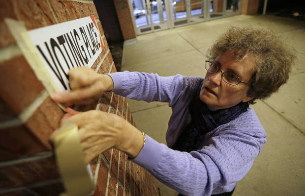 Poll worker Linda Blair hangs a sign before opening Precinct 39 up to allow voters to cast their ballots on Election Day, Tuesday, Nov. 6, 2012, at the First Church of the Open Bible in Des Moines, Iowa. (AP Photo/Charlie Neibergall)