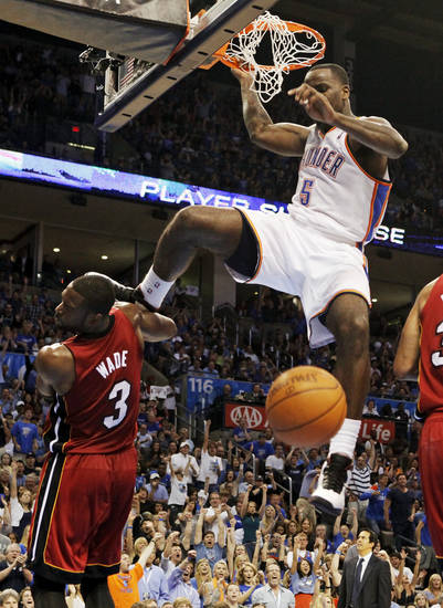 The foot of Oklahoma City's Kendrick Perkins (5) hits Miami's Dwyane Wade (3) in the head after a dunk during the NBA basketball game between the Miami Heat and the Oklahoma City Thunder at Chesapeake Energy Arena in Oklahoma City, Sunday, March 25, 2012. Oklahoma City won, 103-87. Photo by Nate Billings, The Oklahoman