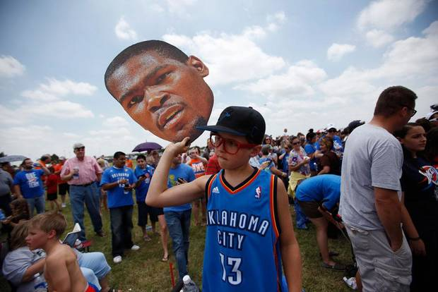 Jack Pitman, 11, of Oklahoma City, holds up a cutout of Kevin Durant's head during a welcome home rally for the Oklahoma City Thunder at a field near Will Rogers World Airport in Oklahoma City, Friday, June 22, 2012.  Photo by Garett Fisbeck, The Oklahoman