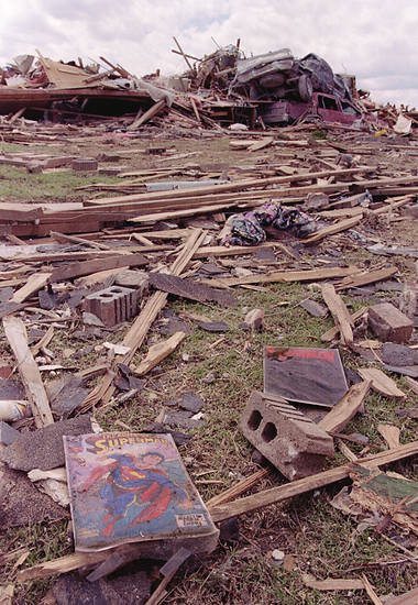 MAY 3, 1999 TORNADO: MAY 3, 1999: Tornado damage: a comic book lay in the yard next to house. In the background a truck from more than a block away rest on ??? cadillac.