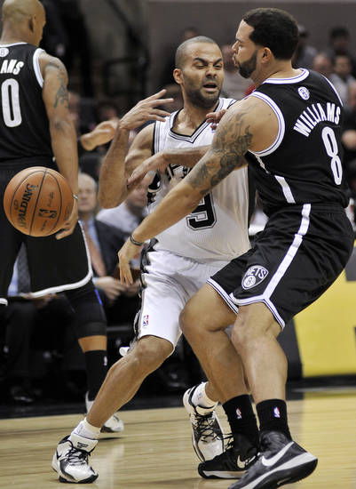 San Antonio Spurs' Tony Parker, center, of France, is defended by Brooklyn Nets' Deron Williams during the first half of an NBA basketball game, Monday, Dec. 31, 2012, in San Antonio. (AP Photo/Darren Abate)
