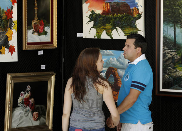 Kevin and Tiffany Durant, Yukon, look at the oil paintings of artist Jim Todd, Sedona, Arizona, during the last day of the Festival of the Arts, Sunday, April 28, 2013. Photo by Doug Hoke, The Oklahoman