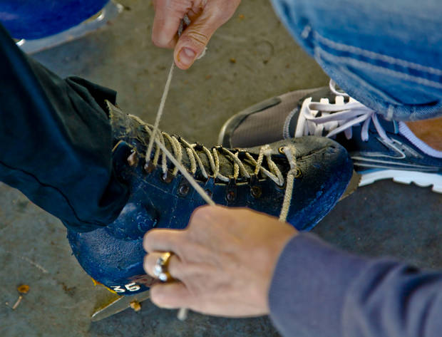 A skater helps with getting the skates laced up at the Edmond outdoor ice skating rink on Sunday, Dec. 2, 2012, in Edmond, Okla.   Photo by Chris Landsberger, The Oklahoman