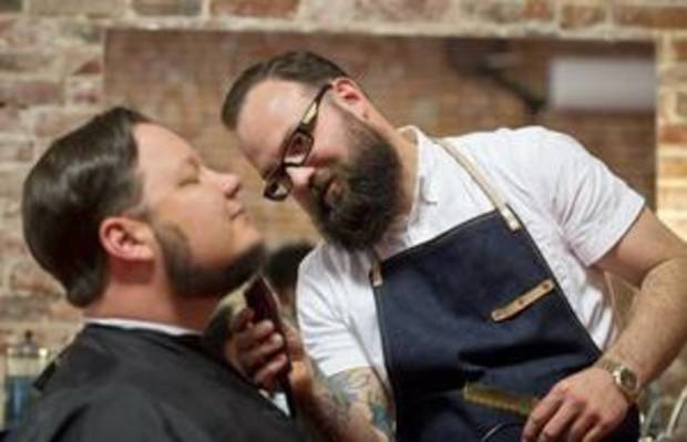 David Eulitt/ Kansas City Star Dane Casey, right, barber at the Calico Beard & Mercantile in Kansas City, Mo., uses clippers to trim the beard of client Jason Domingues.