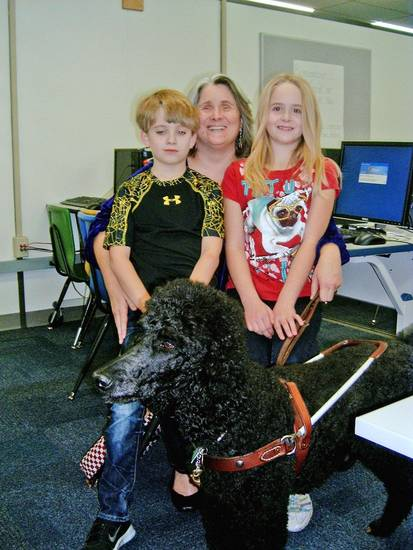 Susan Barker, who is blind, volunteers at Will Rogers Elementary in Edmond, with Jenny, her guide dog. Her children are Elana, 9, and Philip, 8.  Photo by Steve Gust, for The Oklahoman