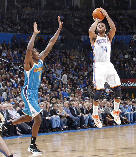 Oklahoma City Thunder shooting guard Daequan Cook (14) shoots a three pointer over New Orleans Hornets shooting guard Marco Belinelli (8) during the NBA basketball game between the Oklahoma City Thunder and the New Orleans Hornets at the Chesapeake Energy Arena on Wednesday, Jan. 25, 2012, in Oklahoma City, Okla. Photo by Chris Landsberger, The Oklahoman