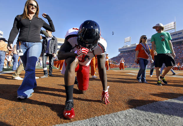 Texas Tech's Tyson Williams (3) kneels for a prayer as fans leave the field before the start of the college football game between the Oklahoma State University Cowboys (OSU) and Texas Tech University Red Raiders (TTU) at Boone Pickens Stadium on Saturday, Nov. 17, 2012, in Stillwater, Okla.   Photo by Chris Landsberger, The Oklahoman