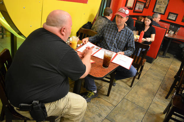 Dustin Merritt, left, of Noble, and Joe Wood, of Norman, carry handguns in holsters on their belts while they catch a midnight snack at Beverly's Pancake House in Oklahoma City on Thursday. <strong>Zeke Campfield - Oklahoman</strong>