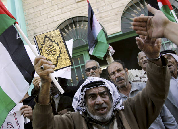   Palestinians, one holding a copy of The Quran, the Muslim holy book, protest against the Israeli military operations in Gaza strip, in the West Bank Al-Fareah refugee camp, Thursday, Nov. 15, 2012. (AP Photo/Mohammed Ballas)  
