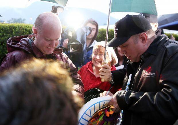 "Garth Brooks, right, signs an autograph for fans after the final taping of ""The Tonight Show with Jay Leno"", in Burbank, Calif., Thursday, Feb. 6, 2014. (AP)"