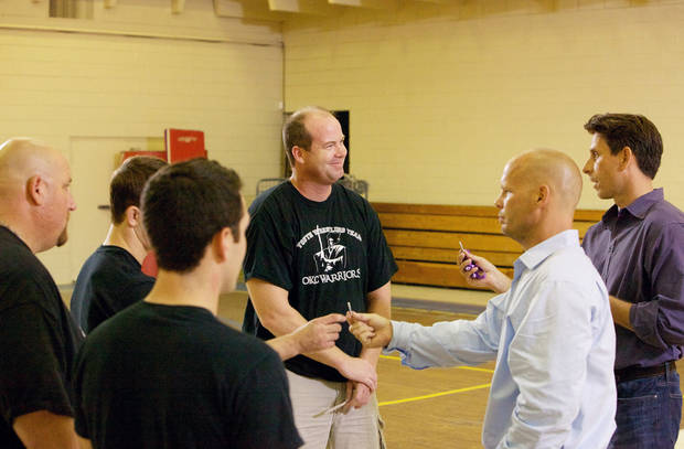 "Leaders of the Oklahoma Wrestling Foundation converse with Dave Mortensen (right of center) and Chuck Runyon during filming of ABC's ""Secret Millionaire"". Mortensen and Runyon are co-founders of Anytime Fitness, a health club chain. PHOTO PROVIDED BY ABC/SHANE BEVEL. <strong>Shane Bevel</strong>"