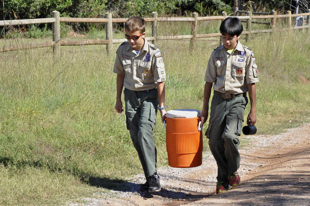 Jacob Garbrecht and Thomas Hara, both of Edmond, carry water to their camp during a Webelos campout on Sept. 21 in Oklahoma City. Photo by M. Tim Blake, for The Oklahoman