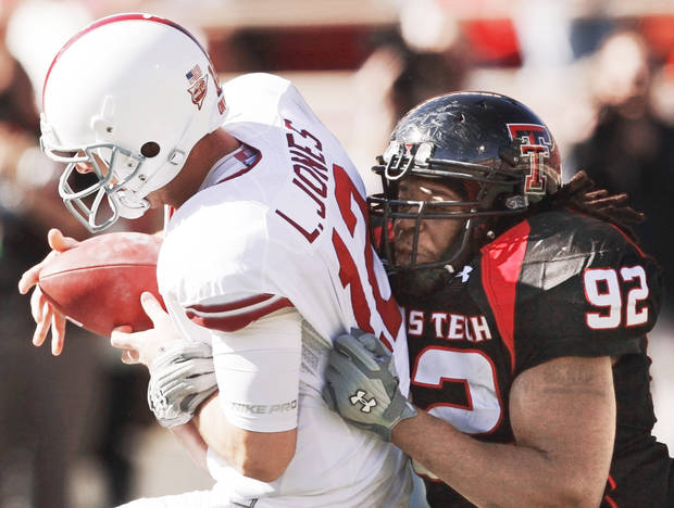 Texas Tech's Brandon Sharpe, right, sacks OU quarterback Landry Jones during action at Jones AT&T Stadium in Lubbock, Texas, on Saturday. Photo by Nate Billings, The Oklahoman