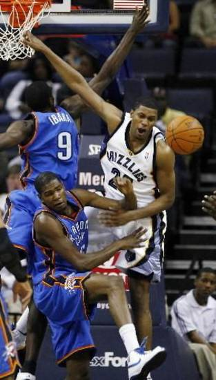 Memphis Grizzlies forward Rudy Gay (22) gets the ball knocked away by Oklahoma City Thunder's  Kevin  Durant (35) and Serge Ibaka (9), of the Republic of Congo, during the first half of a preseason NBA basketball game Wednesday, Oct. 7, 2009, in Memphis, Tenn. (AP Photo/Lance Murphey)