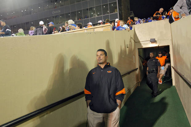 Oklahoma State special teams coach Joe DeForest takes cover as a storm delays the start of the college football game between the Oklahoma State University Cowboys and the University of Tulsa Golden Hurricane at H.A. Chapman Stadium in Tulsa, Okla., Saturday, Sept. 17, 2011. Photo by Chris Landsberger, The Oklahoman