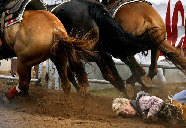 IFYR: Stetson Cravens of Eufaula, Okla. falls to the ground after being dragged by a bucking bronc during the bareback bronc at the International Finals Youth Rodeo in Shawnee, Okla. Thursday, July 16, 2009.  Photo by Ashley McKee, The Oklahoman   ORG XMIT: KOD