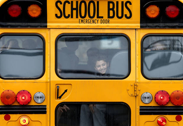 A returning student smiles as his bus school bus pulls into Hawley School, Tuesday, Dec. 18, 2012, in Newtown, Conn.  Classes resume Tuesday for Newtown schools except those at Sandy Hook. Buses ferrying students to schools were festooned with large green and white ribbons on the front grills, the colors of Sandy Hook. At Newtown High School, students in sweatshirts and jackets, many wearing headphones, betrayed mixed emotions.  Adam Lanza walked into Sandy Hook Elementary School in Newtown,  Friday and opened fire, killing 26 people, including 20 children, before killing himself.(AP Photo/Jason DeCrow) ORG XMIT: CTJD108